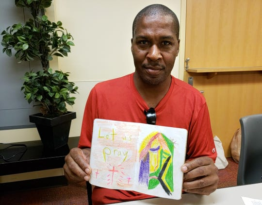 Damon White holds a booklet filled with his artwork, showing an illustration of Jesus.