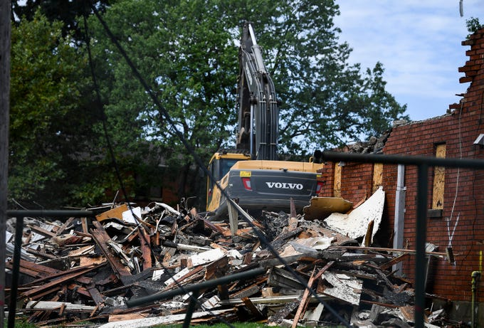 Construction workers demolish old public housing at the James Cayce Homes on a site proposed for a new charter school to be run by the Martha O'Bryan Center  Wednesday, July 18, 2018, in Nashville, Tenn.