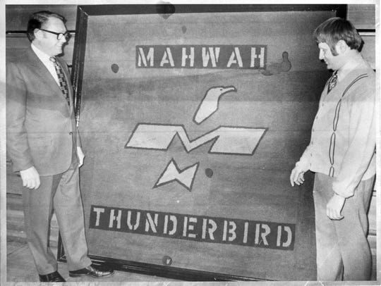 Mahwah High School gets a new treasure in 1973; a hooked rug bearing the school's thunderbird symbol and donated by custodian Doug Schultz; right; and admired by principal Rudolph Knakal.