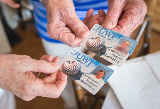 Sheila Pritchett, 82, and her husband Charley Pritchett, 92, show their University of West Florida student ID cards at their home in Pensacola on Thursday, July 19, 2018.  Charley, who holds a bachelor's degree from the University of Cincinnati, and Sheila, who holds a master's degree from Xavier University, are approaching their 40th class that they have audited at UWF together.