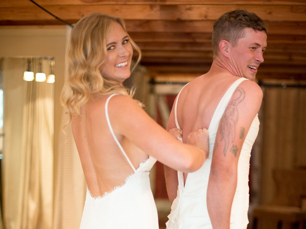 Heidi Zherelyev  (left) dresses her brother Eric Dodds in a wedding gown to play a prank on her husband, Valentin, just before their wedding in Pinetop on June 30, 2018.