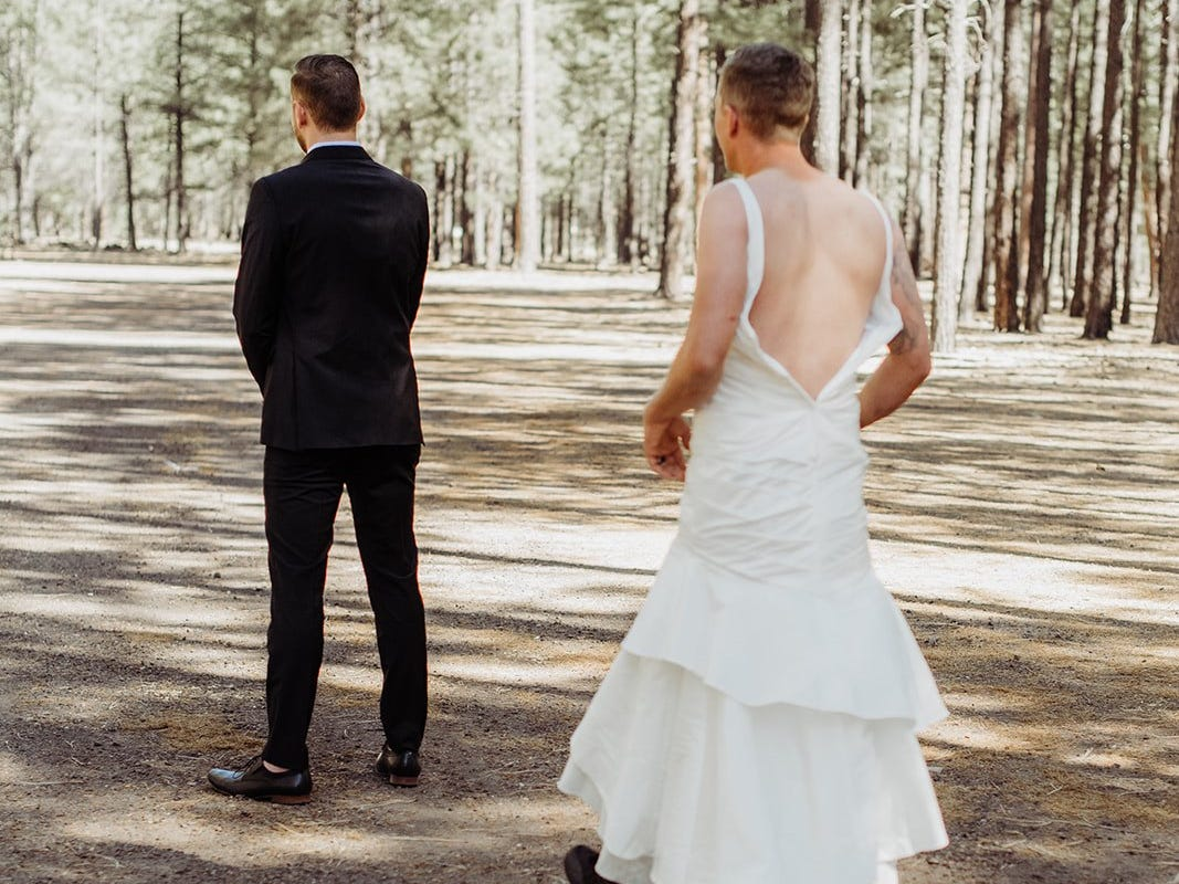 """Eric Dodds, brother of the bride, surprises Tempe groom Valentin Zherelyev during the """"first look"""" photos just before a wedding in Pinetop on June 30, 2018."""