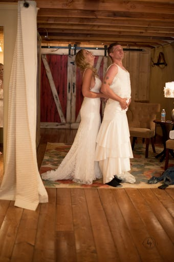 Heidi Zherelyev  (left) laughs while dressing her brother Eric Dodds in a wedding gown to play a prank on her husband, Valentin, just before their wedding in Pinetop on June 30, 2018.