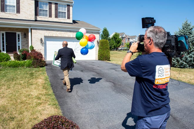 Publishers Clearing House prize patrol member Matt Kelly, left, walks up to the winners home while cameraman Larry Greenblatt records on Thursday, July 19, 2018. Publishers Clearing House awarded a check of $10,000 to Petrena Hamilton, of York County. Hamilton wasn't home at the time, causing the prize patrol to take the check to her at work.