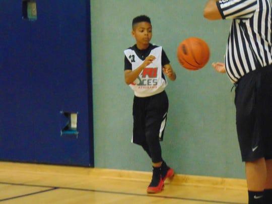 Maurice Douglas Jr. get set to inbound a basketball during a R1 Aces 12U game.