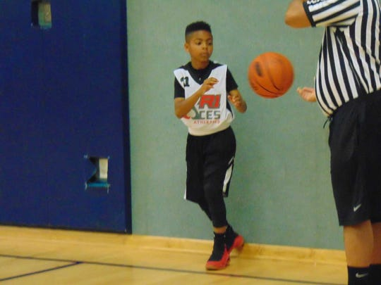 Maurice Douglas Jr. get set to inbound a basketball during a R1 Aces 12U game.
