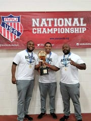 L-R: Coaches Vernon DeShields, Maurice Douglas and Winfield Chandler Jr. pose with the 12U Division III National Championship trophy won by the R1 Aces.