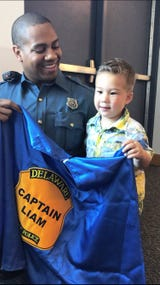 After a chance meeting, Delaware State Police Trooper Michael Young buys Liam Miller, 3, of Bear a birthday gift: a custom-made superhero cape.