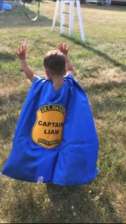 Liam Miller, 3, wears the superhero cape given to him by Delaware State Police Trooper Michael Young.
