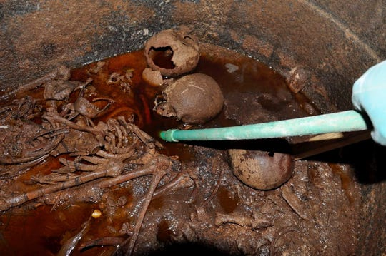 A handout photo made available by the Egyptian Ministry of Antiquities shows workers removing sewer water submerging three decomposed mummies after opening the black granite sarcophagus that was discovered in Sidi Gaber district, Alexandria, Egypt.