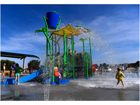 Children run through the falling water after the overhead bucket dumped over them during the grand opening of the Redbud Park Splash Pad July 20, 2018.