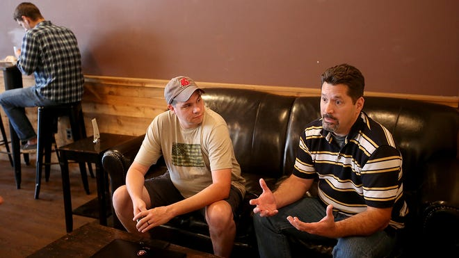 Therapist Dave Secrest, right, and Coffee Oasis's crisis intervention manager Joshua Goss talk about the Oasis Text Line at the Bremerton Coffee Oasis on Friday.