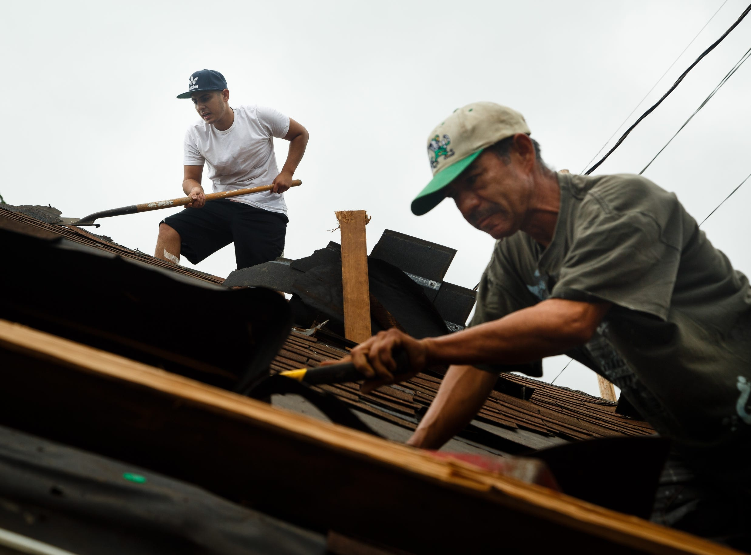 Jose Cervantes, right, and Miguel Ochoa, left, remove the shingles from a blown off roof on Friday, July 20, 2018. Tornadoes swept through central Iowa yesterday causing severe damage but only minor injuries have been reported so far.