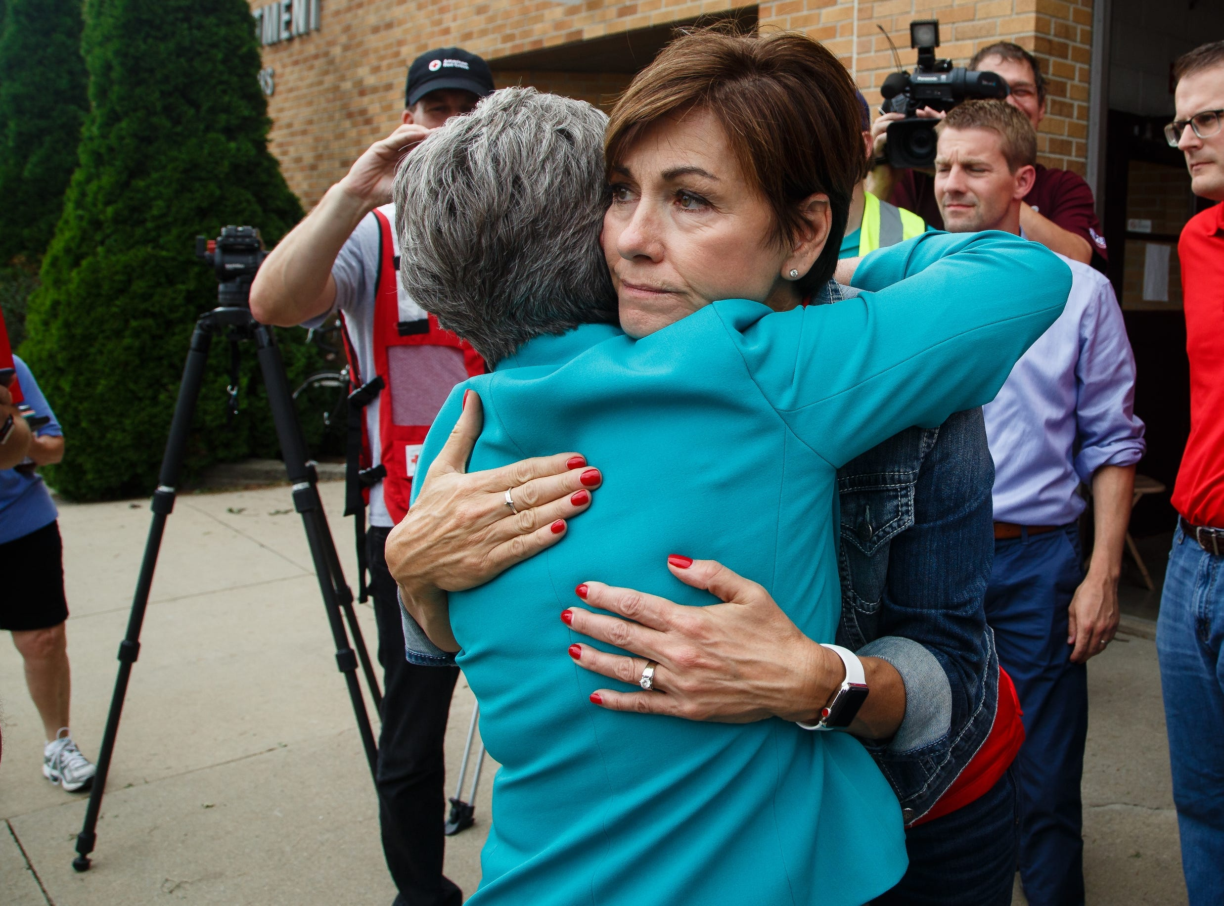 Iowa Governor Kim Reynolds, right, hugs Sen. Joni Ernst as she arrives to tour the damage in Marshalltown on Friday, July 20, 2018. Yesterday, tornadoes ripped through central Iowa causing major damage but only minor injuries have been reported so far.
