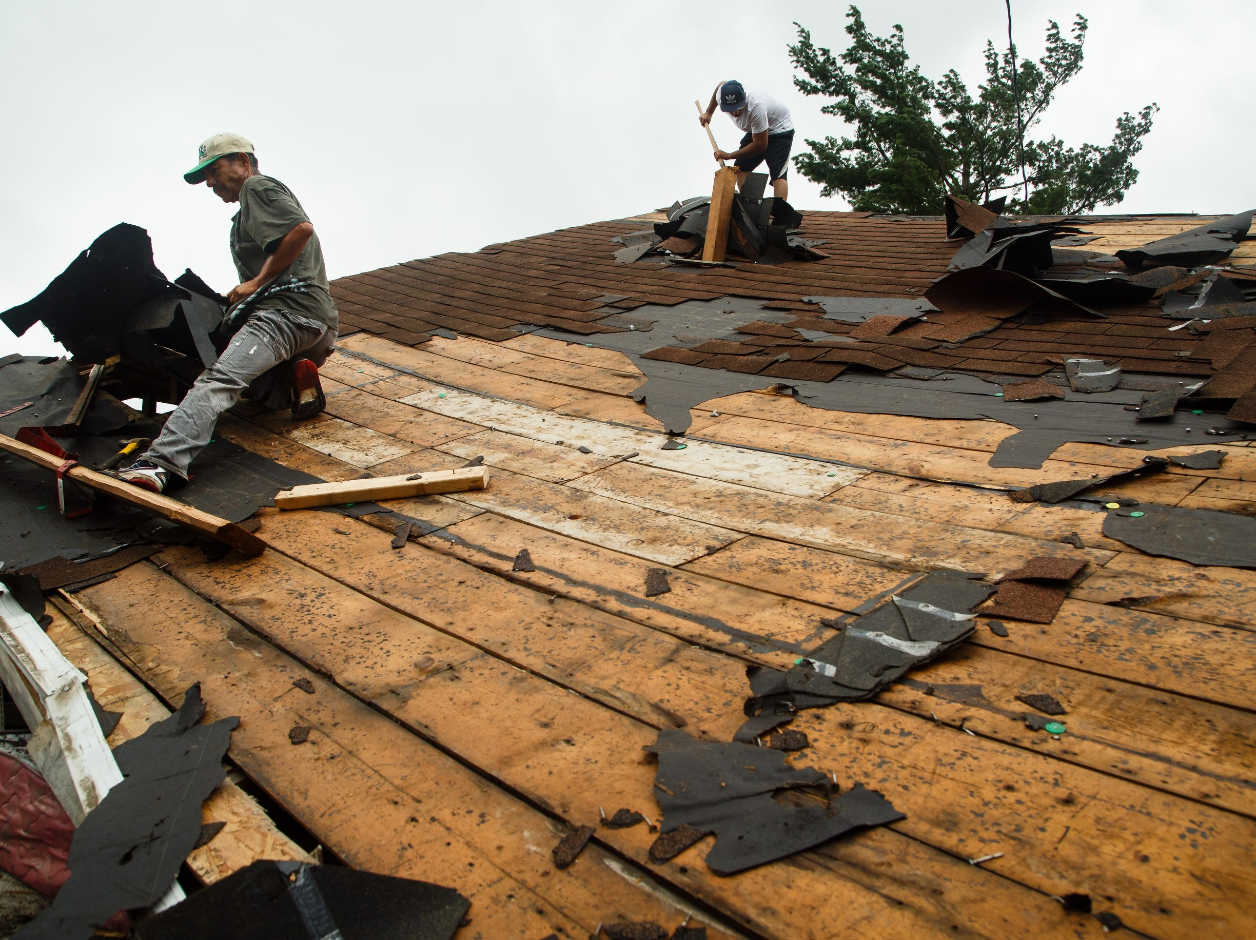 Jose Cervantes, left, and Miguel Ochoa, right, remove the shingles from a blown off roof on Friday, July 20, 2018. Tornadoes swept through central Iowa yesterday causing severe damage but only minor injuries have been reported so far.