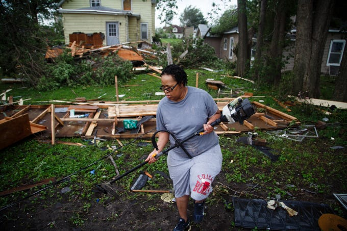 Kassandra McDowell begins to clean up after a tornado swept through Marshalltown on Friday, July 20, 2018.