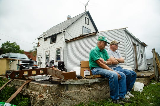 Brothers Dick, left, and Don Ewalt rest as they clean up damage to Don's home on Friday, July 20, 2018. The two have reached lived in Marshalltown for about 50 years but Dick said his home received no damage while Don's roof was nearly torn off and windows blown out.