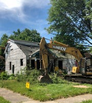 Demolition equipment sits outside a vacant house on Detroit's east side, Wednesday, July 18, 2018.