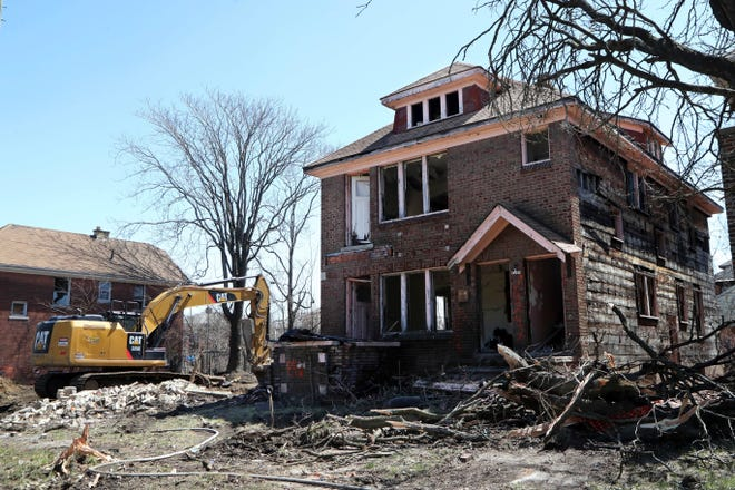 In this Thursday, April 19, 2018, photo, an excavator sits at the site of a house demolition in Detroit.