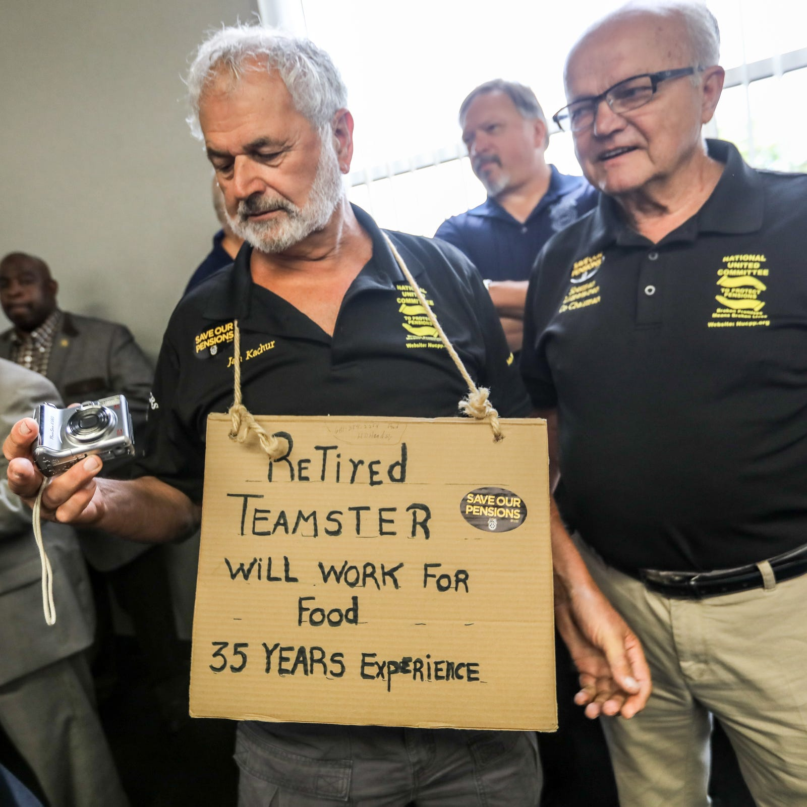 Jan D. Kachur, 75, of Deerfield, Mich. wears a homeless sign saying he will work for food after working for 35 years at Central Transport in Detroit, during a town hall to discuss pensions at the Teamsters Health and Welfare Building in Detroit on Friday, July 20, 2018.