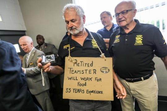 Jan D. Kachur, 75, of Deerfield, Mich., who worked for 35 years at Central Transport in Detroit, wears a homeless sign during a pension town hall on Friday, July 20, 2018.
