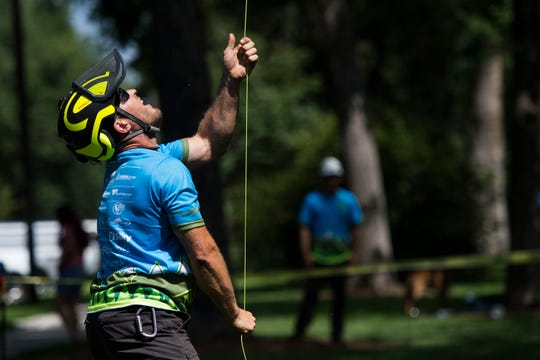Bryan Baer, with BAER Mountain and Urban Forestry, races to pull in his line after stringing it over a branch in the Throwline competition during the annual Tree Climbing Championship for the International Society of Arboriculture's Rocky Mountain Chapter on Friday, July 20, 2018, at City Park in Fort Collins, Colo.