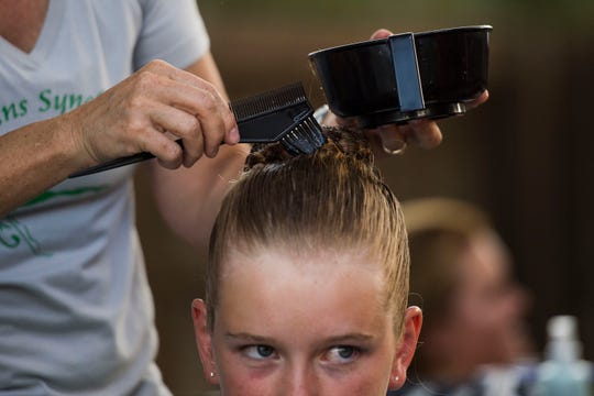 A member of the team has gelatin applied to her hair to help it stay in place before a showcase by the Fort Collins Synchro Team on Thursday, July 19, 2018, at the Village Green Pool in Fort Collins, Colo.