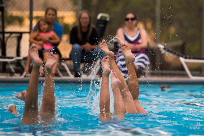 Spectators look onto a team performance during a showcase by the Fort Collins Synchro Team on Thursday, July 19, 2018, at the Village Green Pool in Fort Collins, Colo.