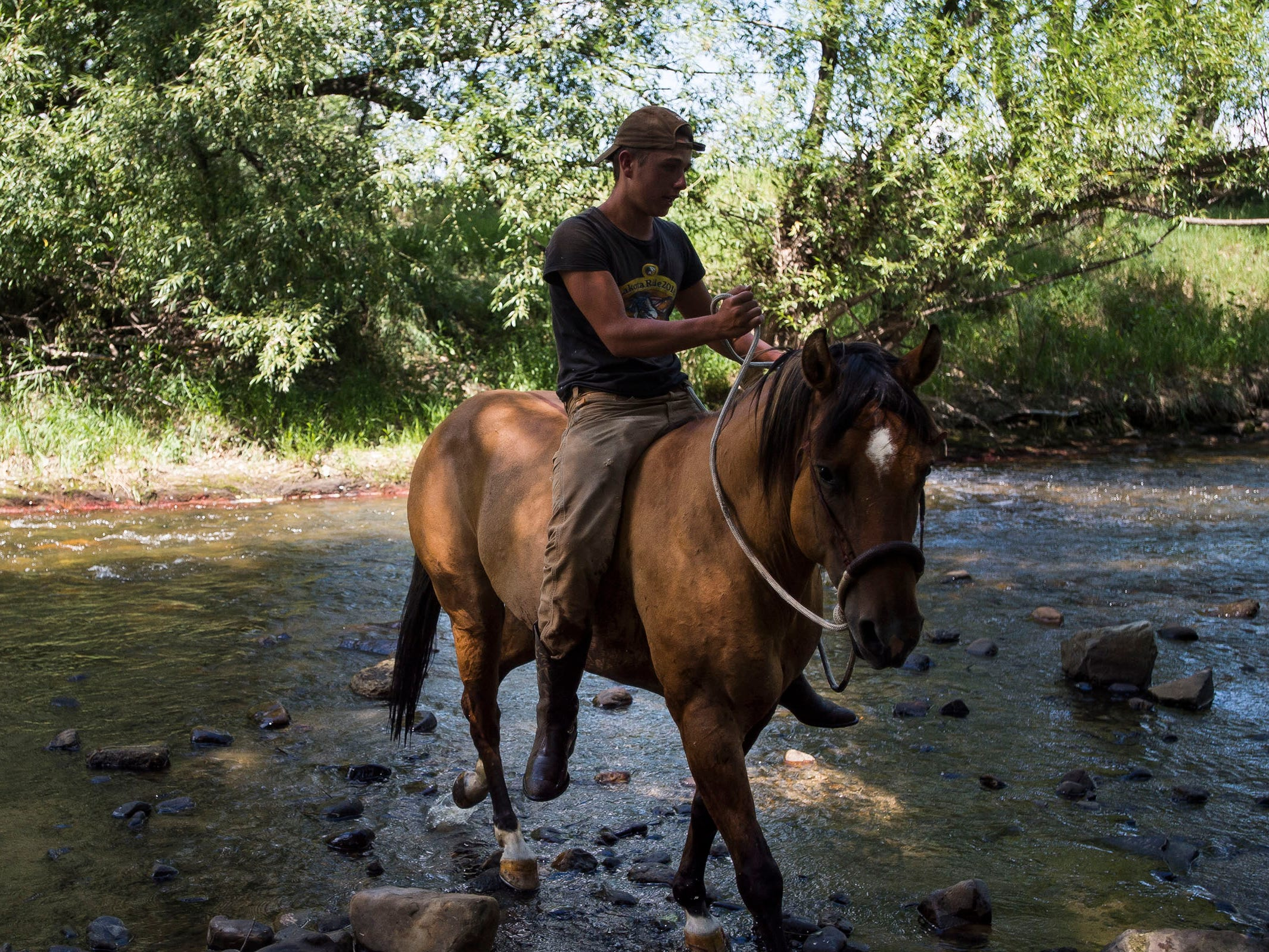 Adam Ventimiglia takes his horse through the river during the LakotaRide 2018 on their way to Namaqua Park on Thursday, July 19, 2018, in Loveland, Colo.