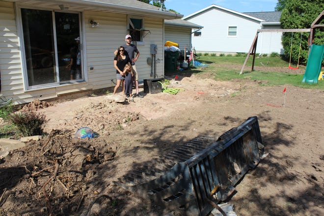 Matt, Brooke and Brinley Sorenson stand in their backyard in Green Bay on July 19, 2018. They have to replace a concrete patio because it heaved after being inundated with water from a water main break in February.