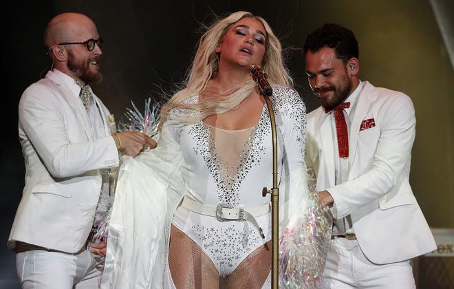 Two dancers/vocalists in Kesha's supporting cast remove a jacket from the singer during the opening segment of Thursday's concert at Ruoff Home Mortgage Music Center.