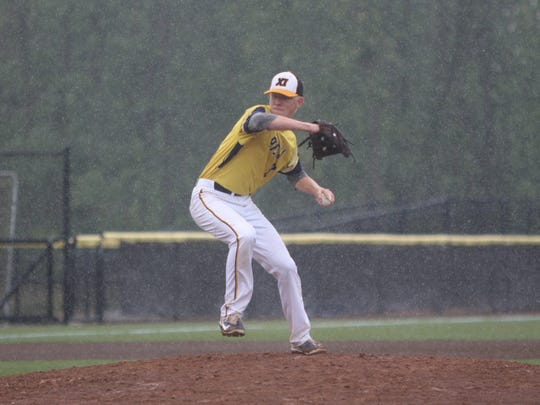 Pius XI pitcher Sam Treffert winds up to deliver to a pitch while rain pours down in a state semifinal against Menomonee Falls on July 20, 2018.