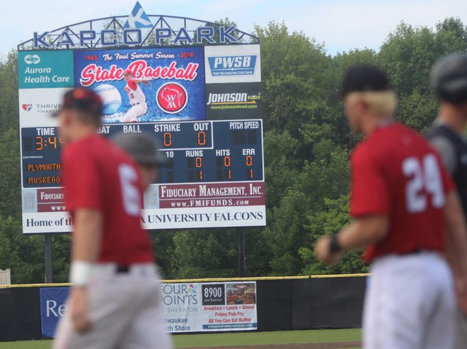 Muskego pitcher Rob Zolecki (24) shakes hands with Plymouth players while the scoreboard at Kapco Park displays the zero hits he gave up in the state semifinal on Friday.