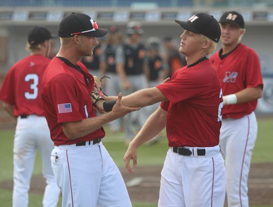 Muskego head coach Jacob Paige (left) and pitcher Rob Zolecki celebrate a 1-0 state semifinal victory over Plymouth on July 20, 2018.