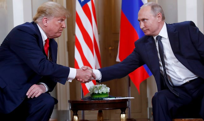 In this July 16, 2018, photo, U.S. President Donald Trump, left, and Russian President Vladimir Putin, right, shake hands at the beginning of a meeting at the Presidential Palace in Helsinki, Finland.
