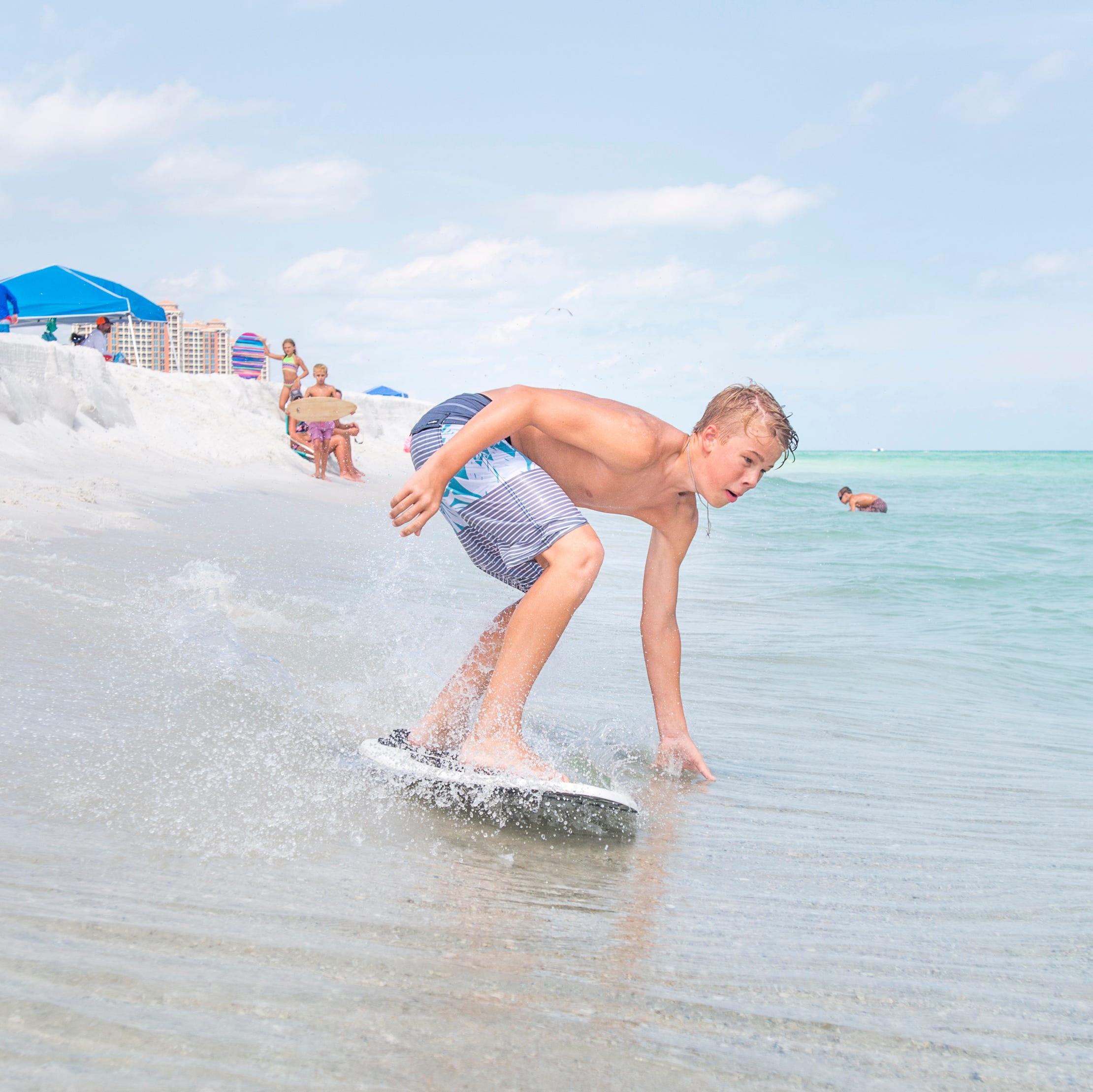 Wyatt West, 14, of New Braunfels, Texas skimboards along Penacola Beach on Friday, July 20, 2018.