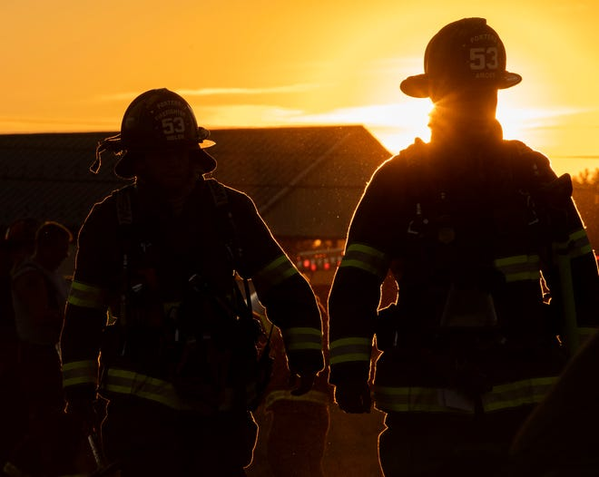 Firefighters walk toward J.F. Rohrbaugh & Co. against the setting sun, Thursday, July 19, 2018. Nearly two dozen units responded to the two-alarm fire at J.F. Rohrbaugh & Co., dispatched at 7:20 p.m.