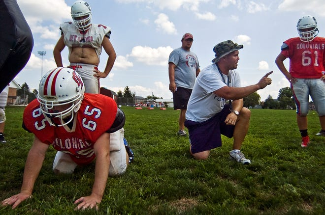 In this file photo from 2012, New Oxford head football coach Jason Thurston shouts out instructions to his players during a blocking drill at the first day of football practice Monday afternoon.