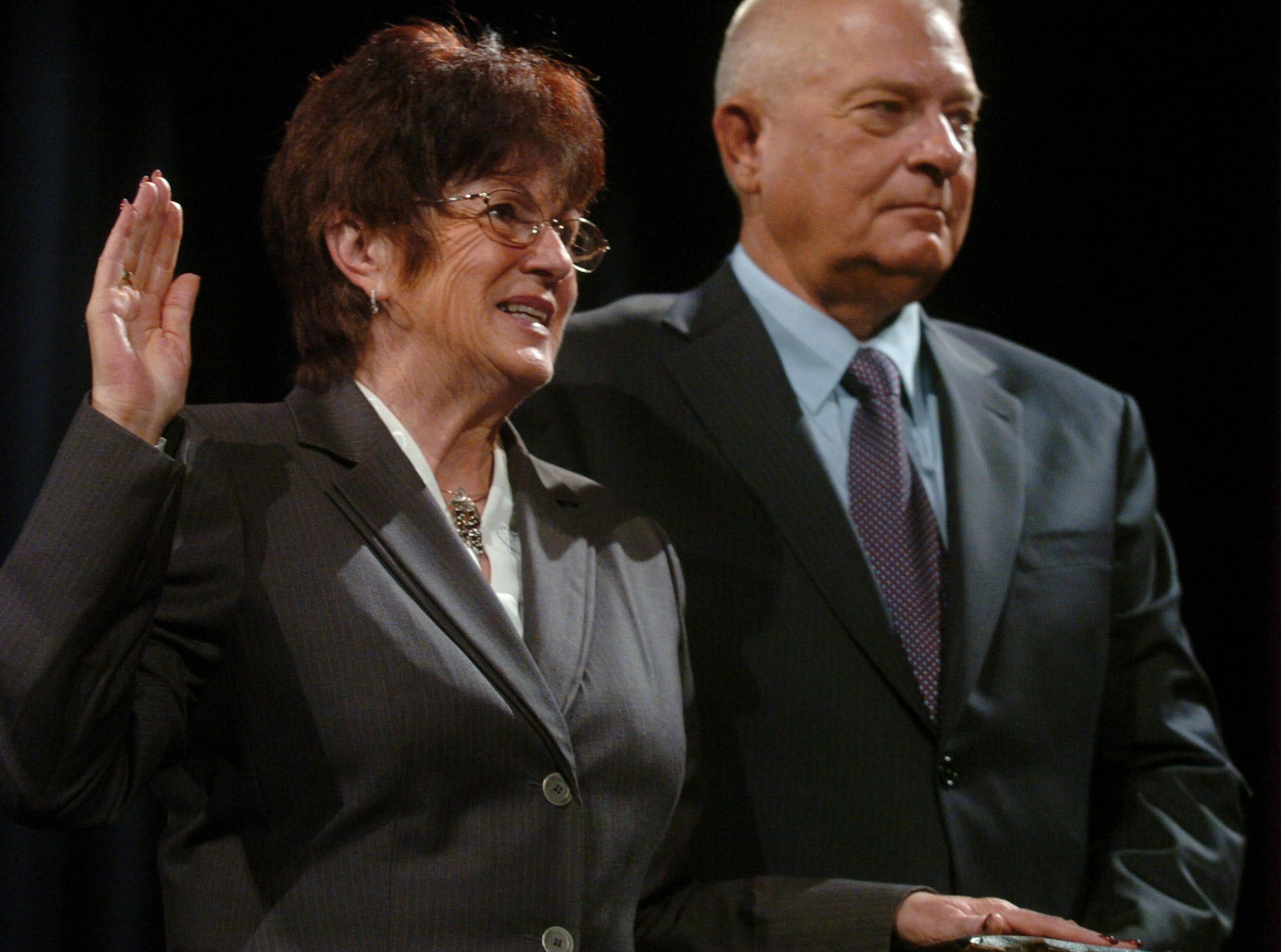 Council member Thelda Williams (left) is sworn into office as her husband, Mel, holds The Bible.