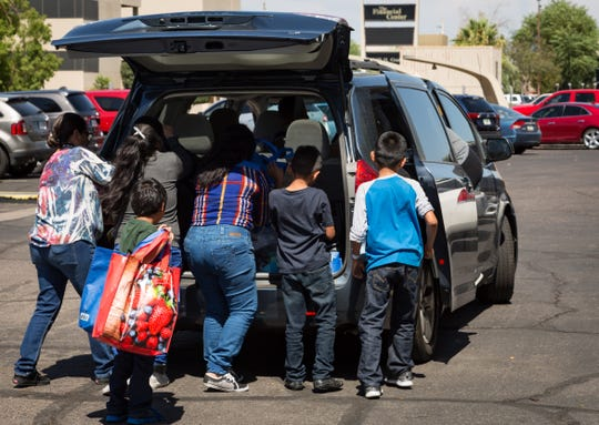 Migrants load up a minivan in Phoenix for a ride to a hotel earlier this week.