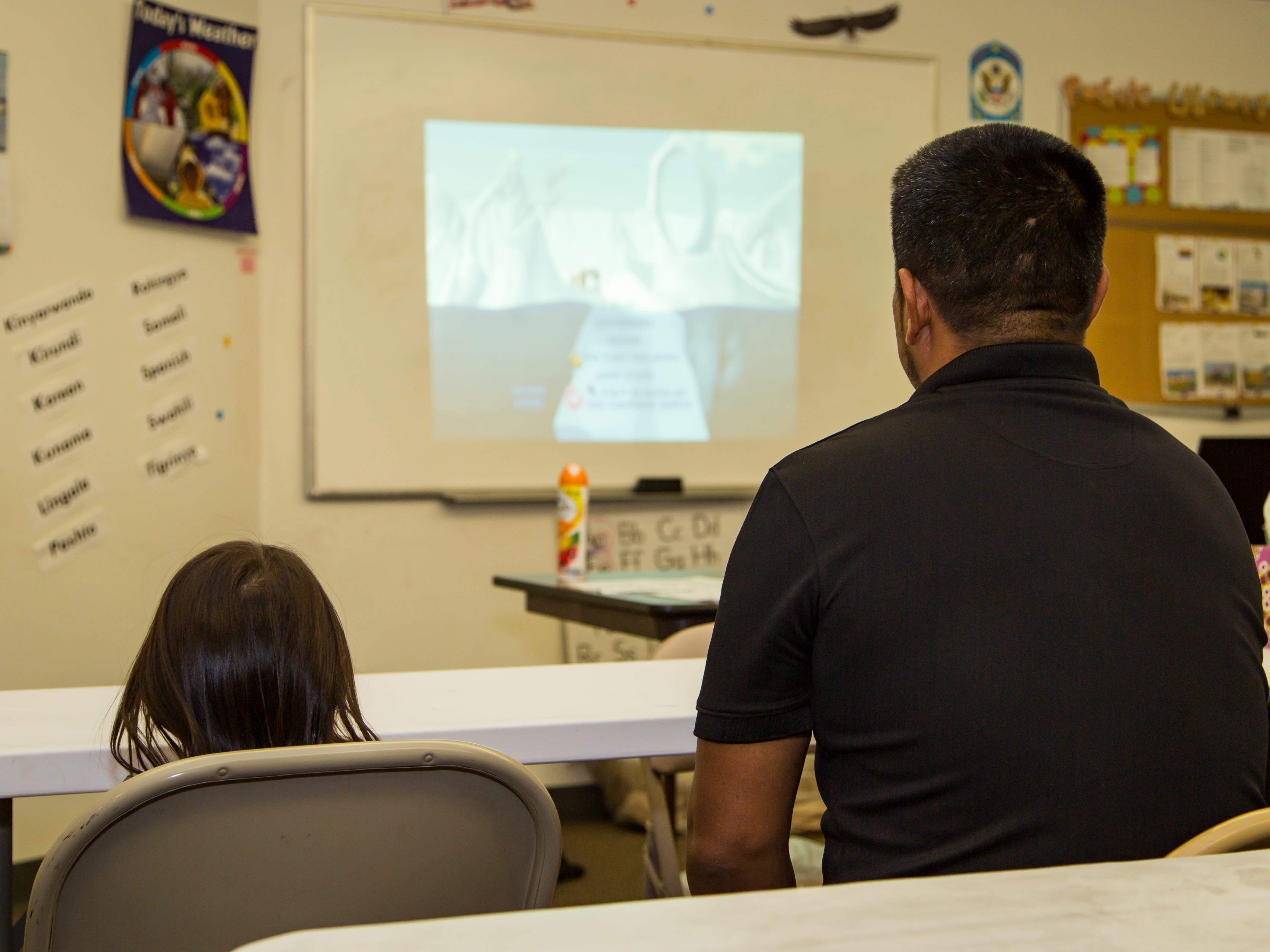 Migrants watch a video in Phoenix.