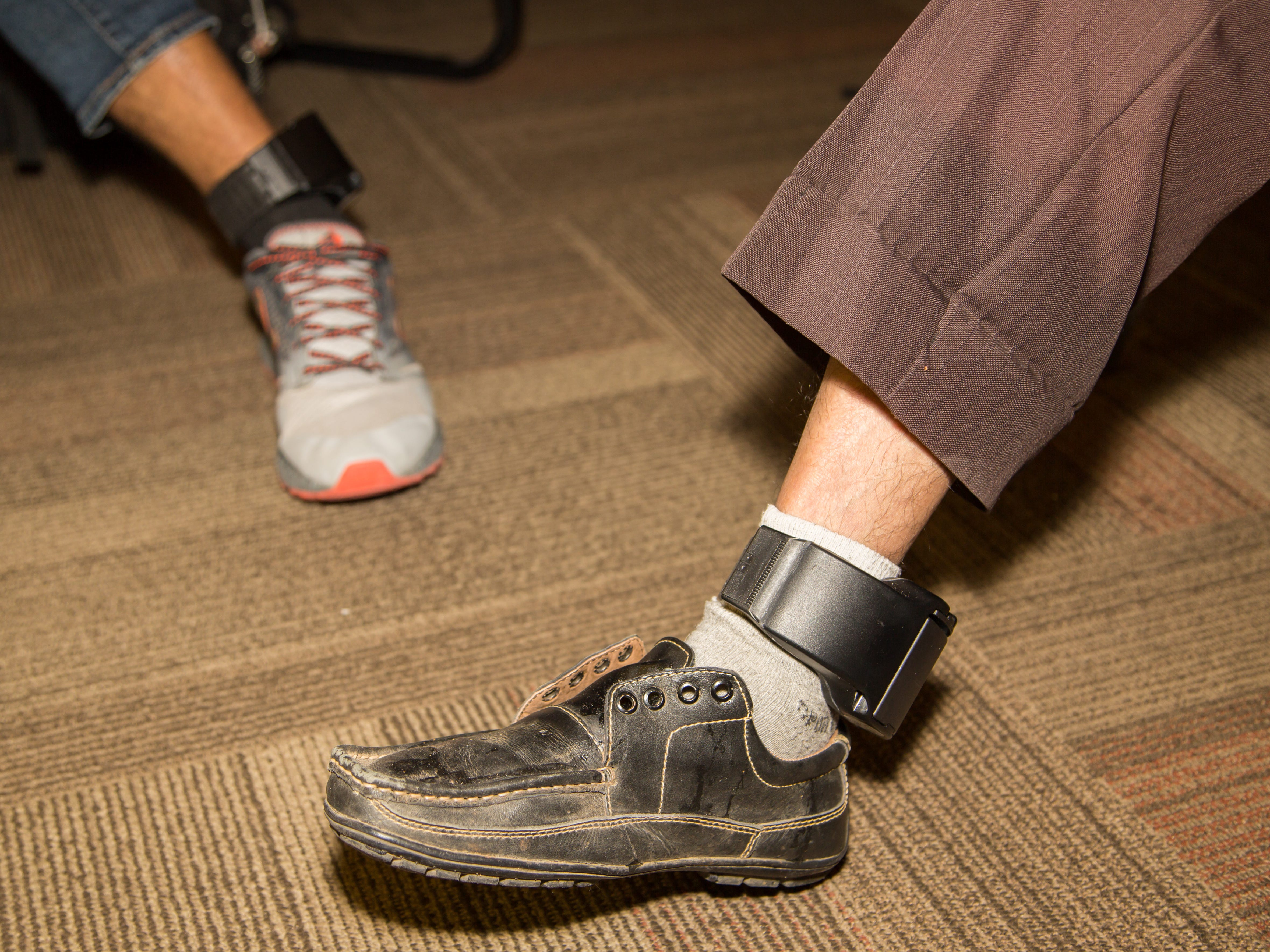 A migrant with an ankle monitor and no shoelaces.
