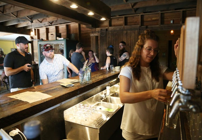 From left, Christopher Bernard of Washington Connecticut and Brian Dooling of Milford Connecticut sit at the bar as Plan Bee Farm Brewing's Owner, Emily Watson, pours a beer in the tasting room of Plan Bee Farm Brewing in the Town of Poughkeepsie on July 20, 2018.