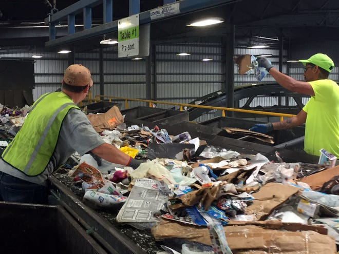 Workers hand pick items out of a conveyer belt that don't belong in recycling.