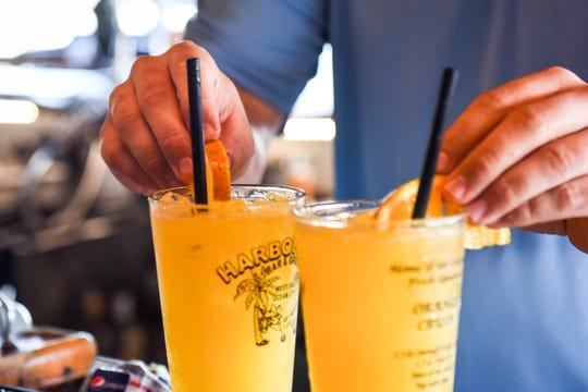 Harborside Bar & Grill manager Phil Lewis tops off orange crush drinks with slices of orange on Thursday, July 20.