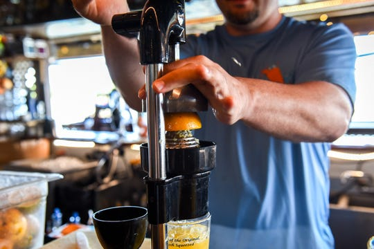 Harborside Bar & Grill manager Phil Lewis crushes a fresh orange into an orange crush drink on Thursday, July 20.