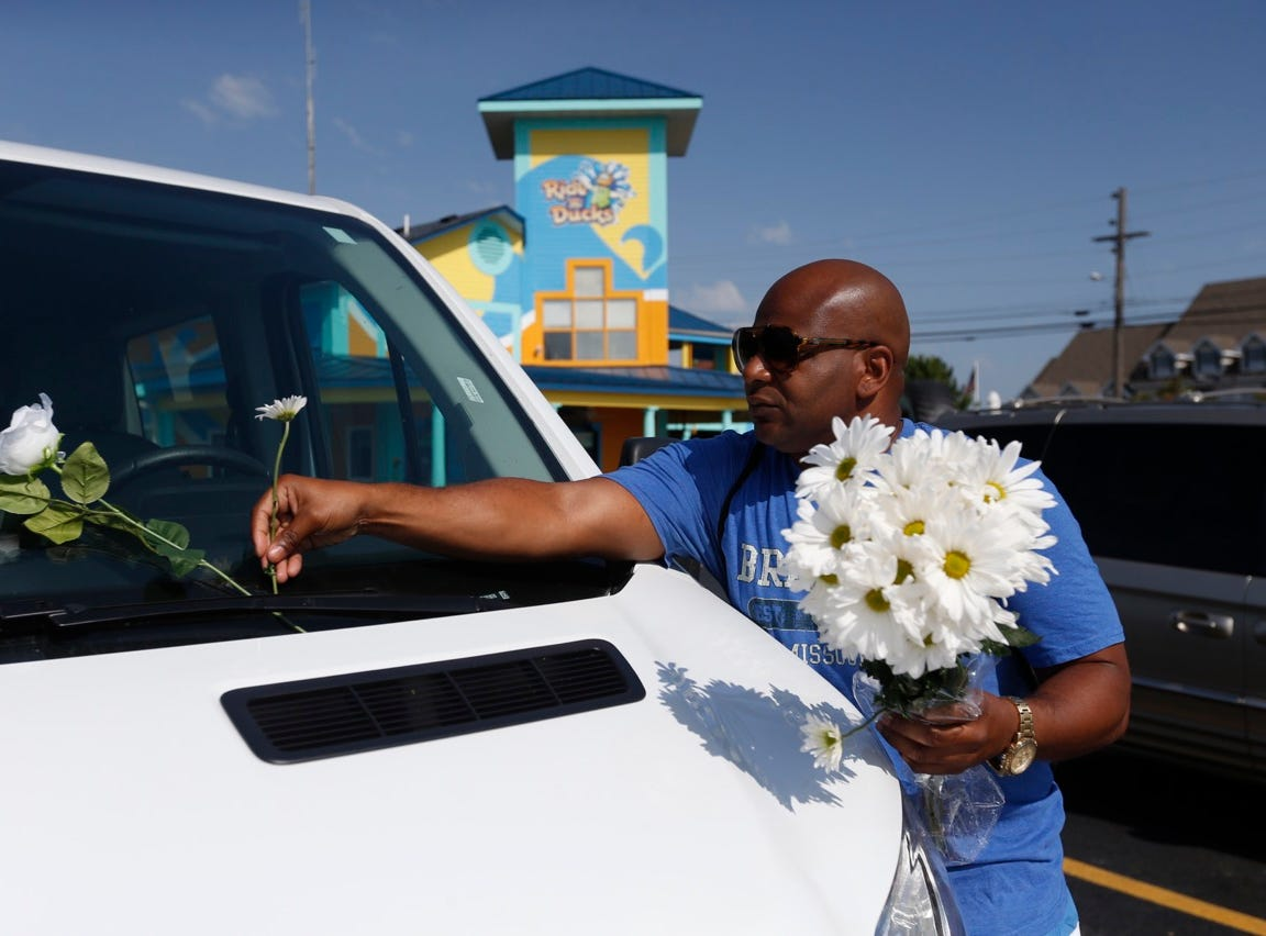 Guain Holloman, of Tennessee, places a flower on the windshield of a car in the Ride the Ducks parking lot in Branson on Friday.