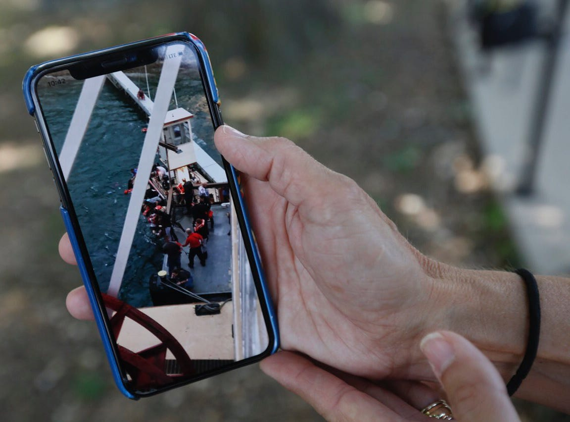 Sonja Malaske, of Harrah, Oklahoma, shows a picture she took from the Branson Belle of people being pulled from the water after a Ride the Ducks amphibious vehicle capsized on table Rock Lake on Thursday night.