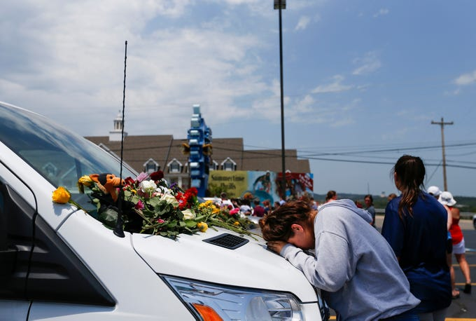 A woman prays on the hood of a van  left in the parking lot of Ride the Ducks on Friday, July 20, 2018 after a duck boat sank killing 17 people.