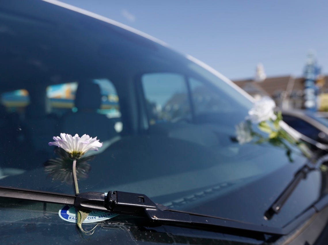 Flowers are placed on the windshield of cars in the Ride the Ducks parking lot in Branson on Friday.